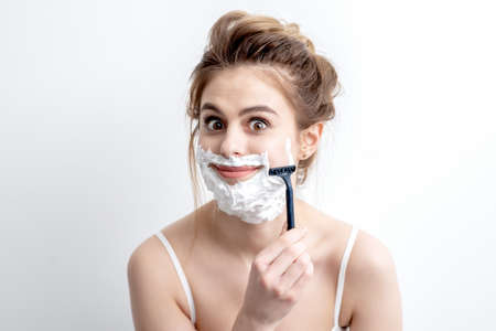Beautiful young caucasian woman shaving her face by razor on white background. Pretty woman with shaving foam on her face Archivio Fotografico