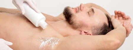 Hand of master depilation pouring talcum powder on armpit of young man before depilation procedure.
