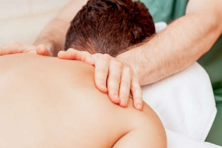 Young man receiving back massage by hands of masseur in spa beauty salon.