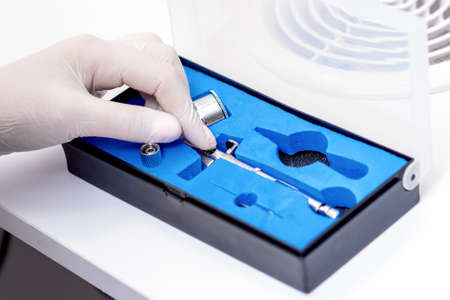 Human hand in protective glove taking out airbrush tool for painting nails from the box in salon