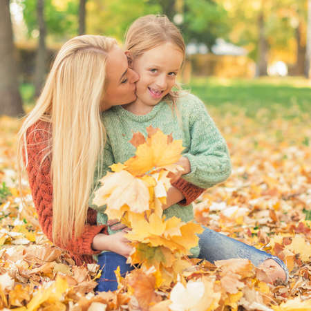 Happy young caucasian mother and little daughter holding autumn yellow leaves sitting and kissing at the park