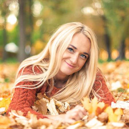 Beautiful young blond hair caucasian woman lies down on leaves at the autumn park Фото со стока