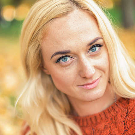 Portrait of beautiful young blond hair caucasian woman looking at camera at the Autumn Park 版權商用圖片