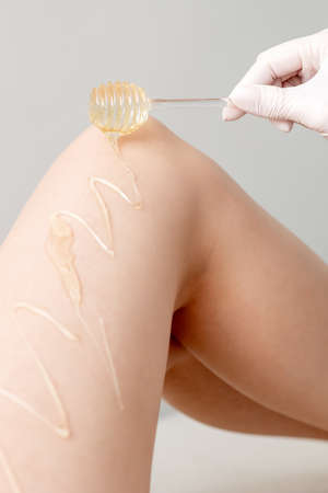 Wax on honey stick flowing down on female leg in human hand wearing protective glove on white background Reklamní fotografie
