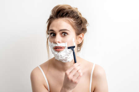 Beautiful young caucasian woman shaving her face by razor on white background. Pretty woman with shaving foam on her face 免版税图像