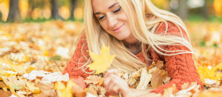 Beautiful young blond hair caucasian woman lies down on leaves at the autumn park Archivio Fotografico