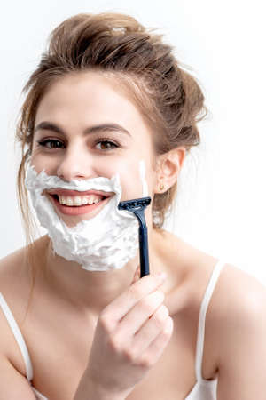 Beautiful young caucasian woman shaving her face by razor on white background. Pretty woman with shaving foam on her face Foto de archivo