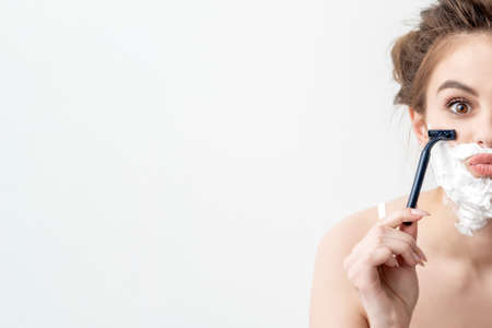 Beautiful young caucasian woman shaving her face by two razors on white background. Pretty woman with shaving foam on her face