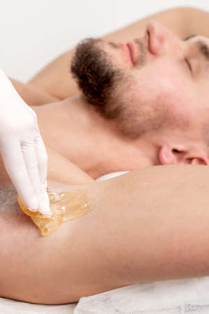 Depilation and epilation male armpit with liquid sugar paste. Hand of cosmetologist applying wax paste on armpit of man. Smooth underarm concept