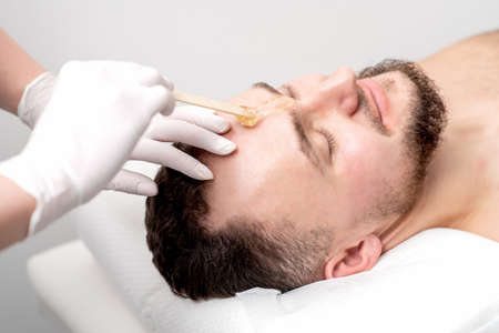 Beautician applies wax between male eyebrows before the procedure of waxing in the beauty salon Foto de archivo