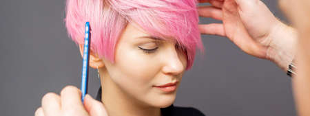 Hairdresser checking short pink hairstyle of young woman on gray background Standard-Bild