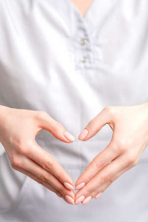 Close up of female hands making heart shape. Romantic concept.