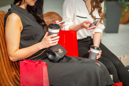 Two beautiful caucasian young women looking in smart phone with bags sitting on the bench while resting in the shopping mall