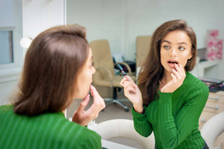 Beautiful young caucasian woman applying gloss to the lips by finger looking in the mirror