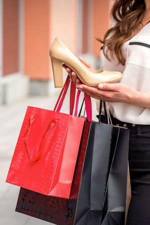 Young female holding new high heel shoe after shopping standing with bags near shopping mall outdoor