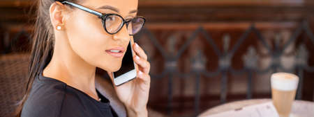 Beautiful young caucasian businesswoman wearing glasses makes call by cell phone at cafe Banque d'images