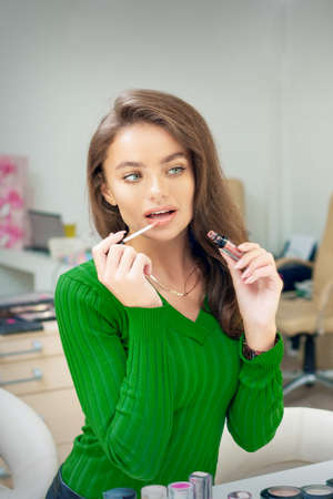 Beautiful young caucasian woman applying gloss to the lips looking in the mirror