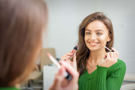 Beautiful young caucasian smiling woman applying gloss to the lips looking in the mirror