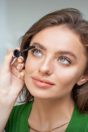 Professional makeup artist applying mascara on lashes of beautiful young caucasian woman in beauty salon