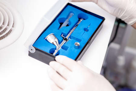 Close up shot of manicure master hand is taking out new clean airbrush tool for nails wearing gloves from the blue box
