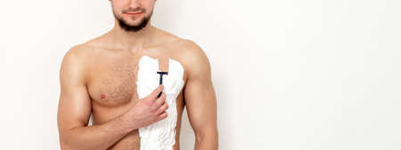 Young caucasian man with beard holds razor shaves his chest with white shaving foam on white background. Man shaving his torso