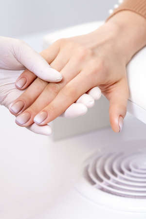 Female hand after manicure in hand of manicure master at nail salon 免版税图像