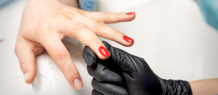 Young woman receives red nail polish by professional manicure master in nail salon