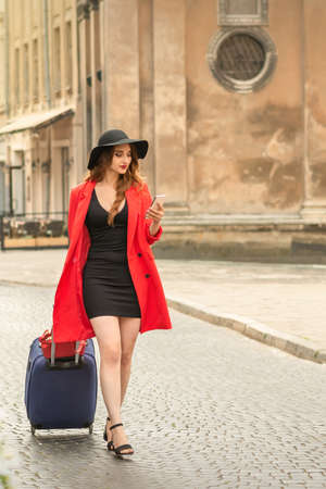 Beautiful fashionable young brunette woman walking at city street with travel suitcase and smartphone 写真素材