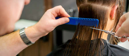 Close up of hands of male hairdresser cutting long hair of young woman holding scissors and comb at the salon. Rear view