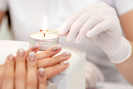 Manicure master in white gloves lighting candle with match in nail salon