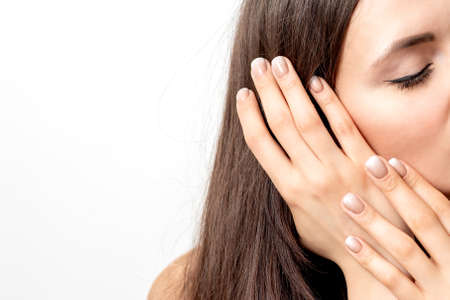 Side view portrait of beautiful young caucasian brunette woman with closed eyes touching her hair by manicured fingers on white background