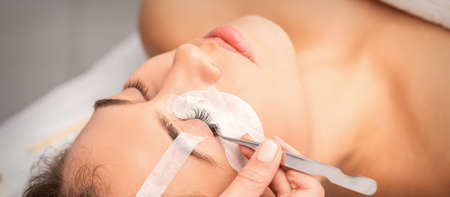 Young caucasian woman having eyelash extension procedure in beauty salon. Beautician glues eyelashes with tweezers