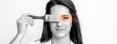 Black and white portrait of young woman painting her eye in yellow color with paintbrush on white background