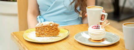 Sweet different pieces of cake on the plates at the table on a womans background with a cup of coffee in a cafe