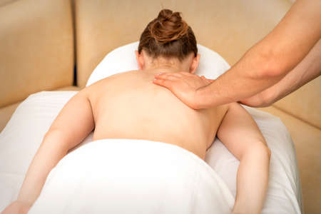 Hands of a masseur massaging back of a young adult woman in spa salon