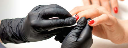 Close up of manicure master leaks female red nails with a lint-free napkin in a nail salon Stock fotó
