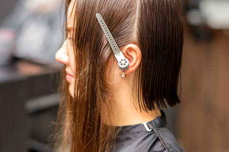 Close up side view of young brunette caucasian woman with split hair in sections in a hair salon Stock Photo