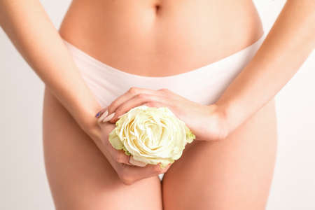 Young woman's hands holding a white flower covering epilate bikini zone isolated on white studio background. Concept of female health, reproductive, gynecology Standard-Bild