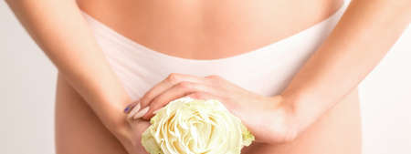 Young womans hands holding a white flower covering epilate bikini zone isolated on white studio background. Concept of female health, reproductive, gynecology