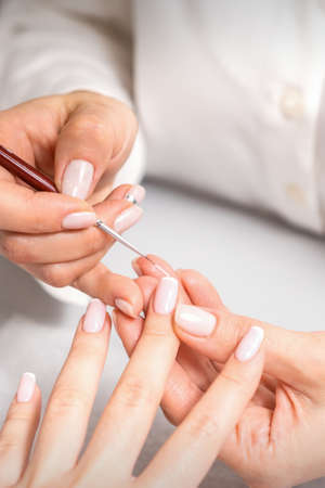 French manicure. Manicure master drawing white varnish on the nail tip with a thin brush, close up
