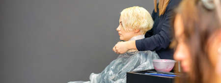 The female hairdresser puts on a transparent cellophane cape to the female client in a beauty hair salon