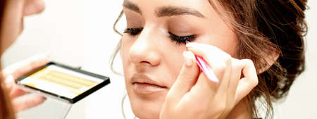 Eyelash extension procedures. Beautiful young caucasian woman receiving eyelash extension by master in a beauty salon Archivio Fotografico