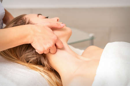Beautician making lymphatic drainage face massage or facelifting massage at the beauty salon