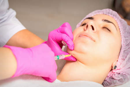 The cosmetologist makes lipolytic injection on the chin of a young woman against the double chin in a beauty salon Stock Photo
