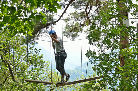 Teenage boy is climbing on the trapeze bar at the rope parkour outdoors  He is photographed from below against the green forest Stock Photo - 24257508