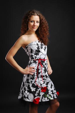cocktaildress: Een krullend jonge vrouw in de cocktail jurk met bloemmotief op de donkere achtergrond
