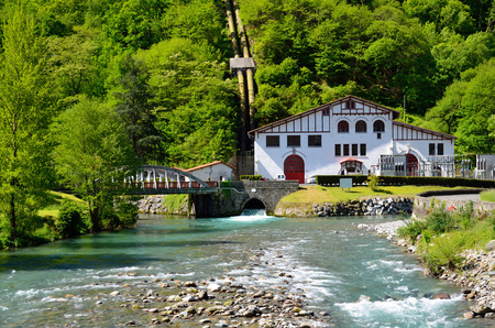 forested: Small hydroelectric power station is situated near the swift river under the forested mountain in the Pyrenees  Its building is made in the traditional Basque style   Stock Photo
