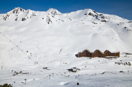There are downhills, aerial lifts, skiers and hotels on the snow slopes in the winter Pyrenees   photo