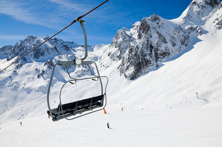 A chair of the aerial lift is photographed close-up against the snow downhill with skiers in the winter Pyrenees  photo