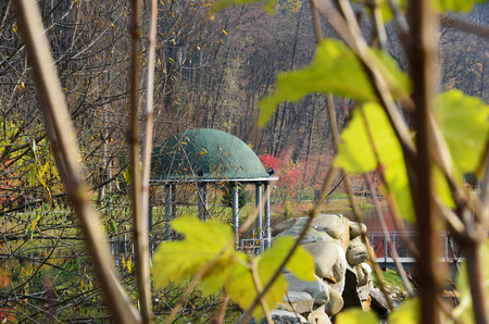 The round pavilion is photographed through bare twigs with yellow leaves in the autumn garden  photo